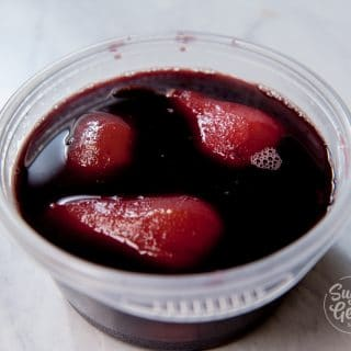 cooling poached pears in hot red wine poaching liquid to deepen the color