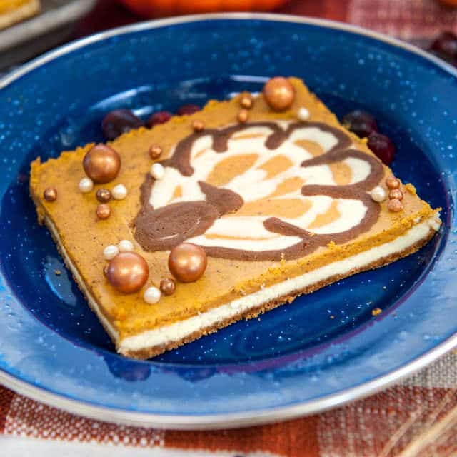 pumpkin cheesecake bars with turkey piped on top on blue plate