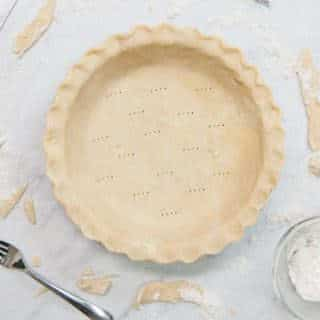 pie dough that has been rolled out into a pie plate and edges have been fluted
