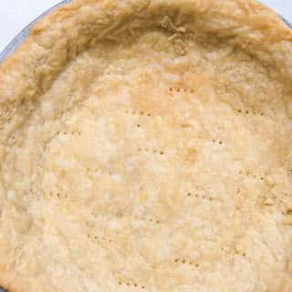 closeup of flakey pie dough in a pie pan that has been blind baked