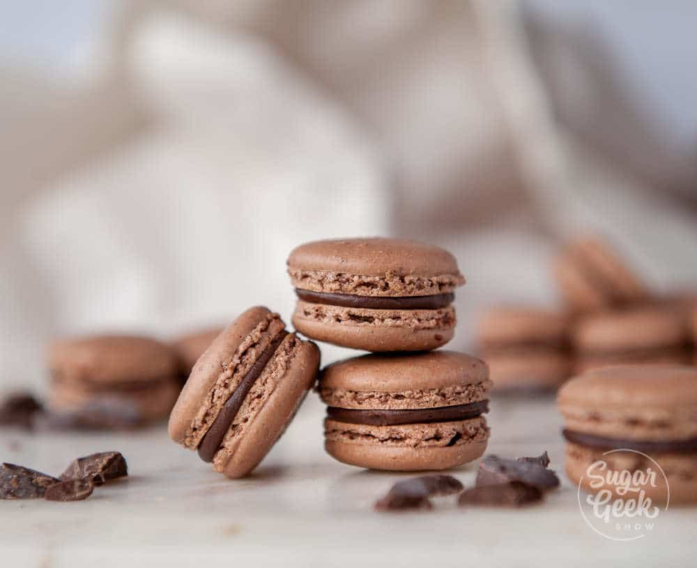 close up of three chocolate macarons with ganache filling