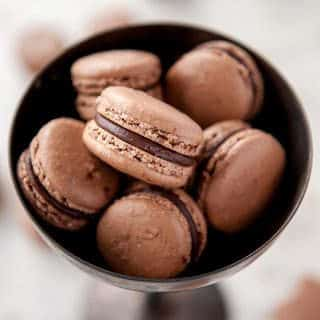 closeup of chocolate macarons in metal bowl