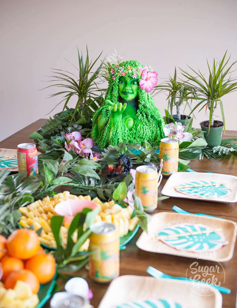 table decorated with luau themed decorations and moana tifiti birthday cake