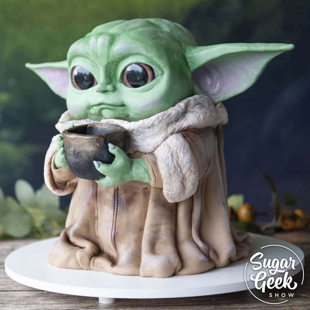 Learn how to make the baby Yoda cake from instructor Elizabeth Marek of Sugar Geek Show. You will learn how to create a sculpted baby yoda from rice cereal treats or from similarly sized cake rounds. Elizabeth shows how to make step-by-step edible eyeballs, how to sculpt the face and measure the proportions of the face. Techniques on realistic skin tones, adding shadow and depth are covered, as well as how to make the clothing and textures. Over an hour and a half of step-by-step instructions and tips, along with additional printable templates. Recommended for intermediate cake decorators.