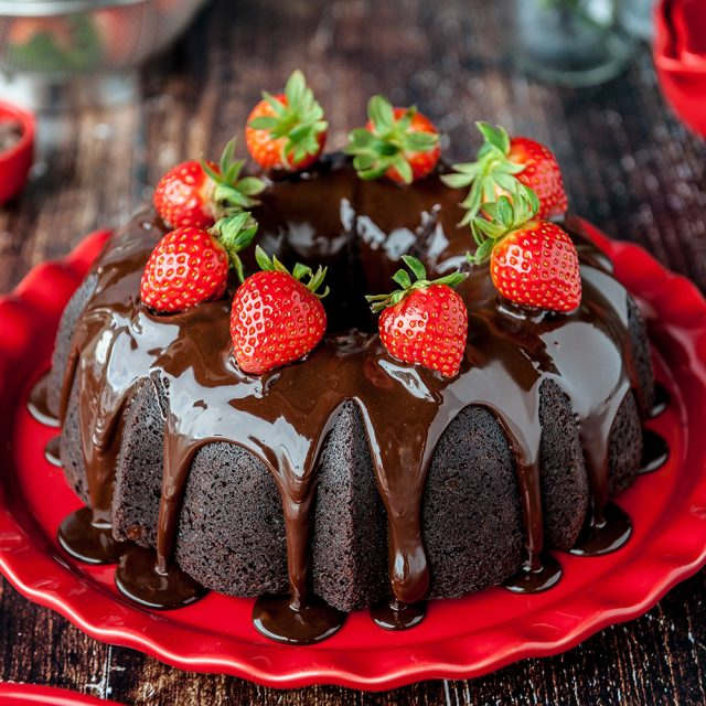 chocolate bundt cake with chocolate ganache and strawberries on a red plate