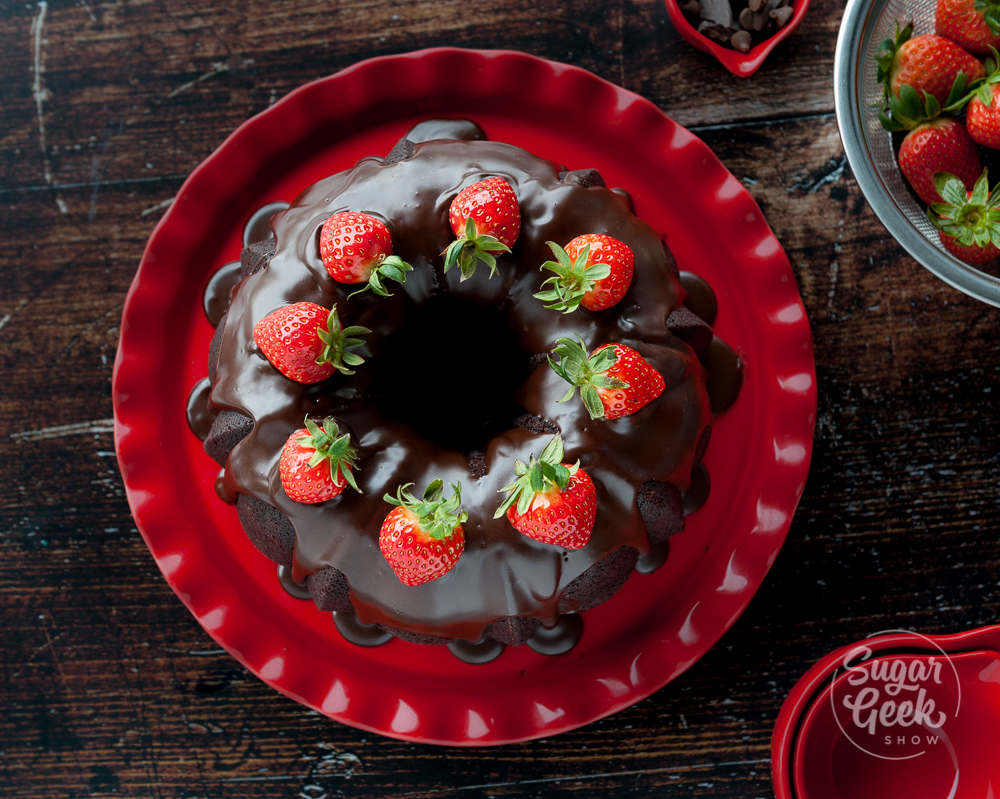 chocolate bundt cake with shiny chocolate glaze and fresh strawberries