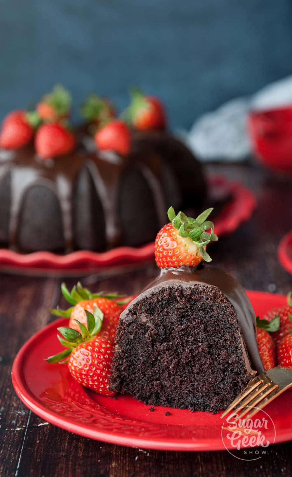 close up of a slice of chocolate bundt cake with ganache and fresh strawberries. Bundt cake in the background