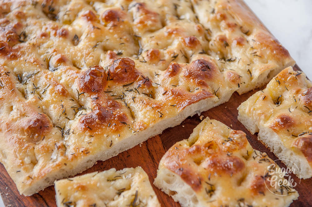 focaccia bread sliced into squares on a wooden cutting board