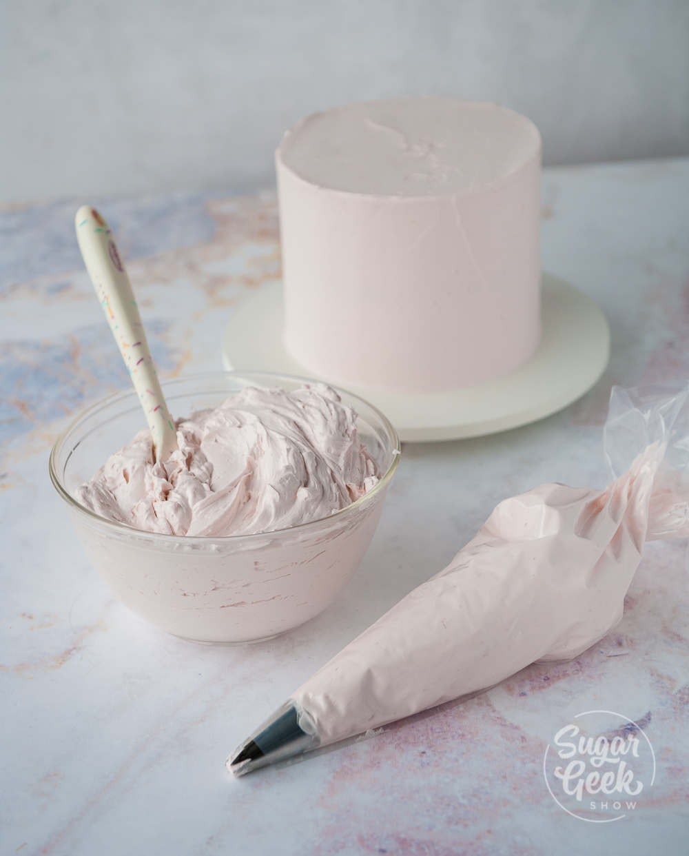 italian meringue buttercream in a bowl, piping bag and frosted no a cake