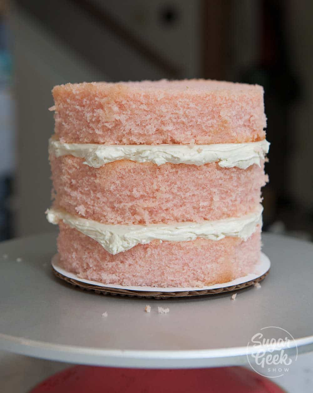 three layers of pink velvet cake with whipped cream in between the layers