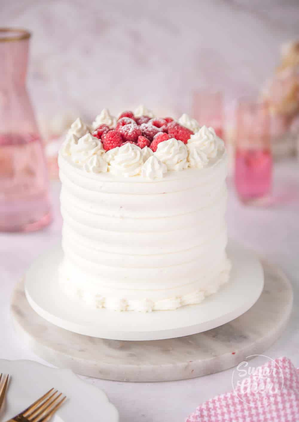 pink velvet cake frosted in stabilized whipped cream with fresh raspberries on top