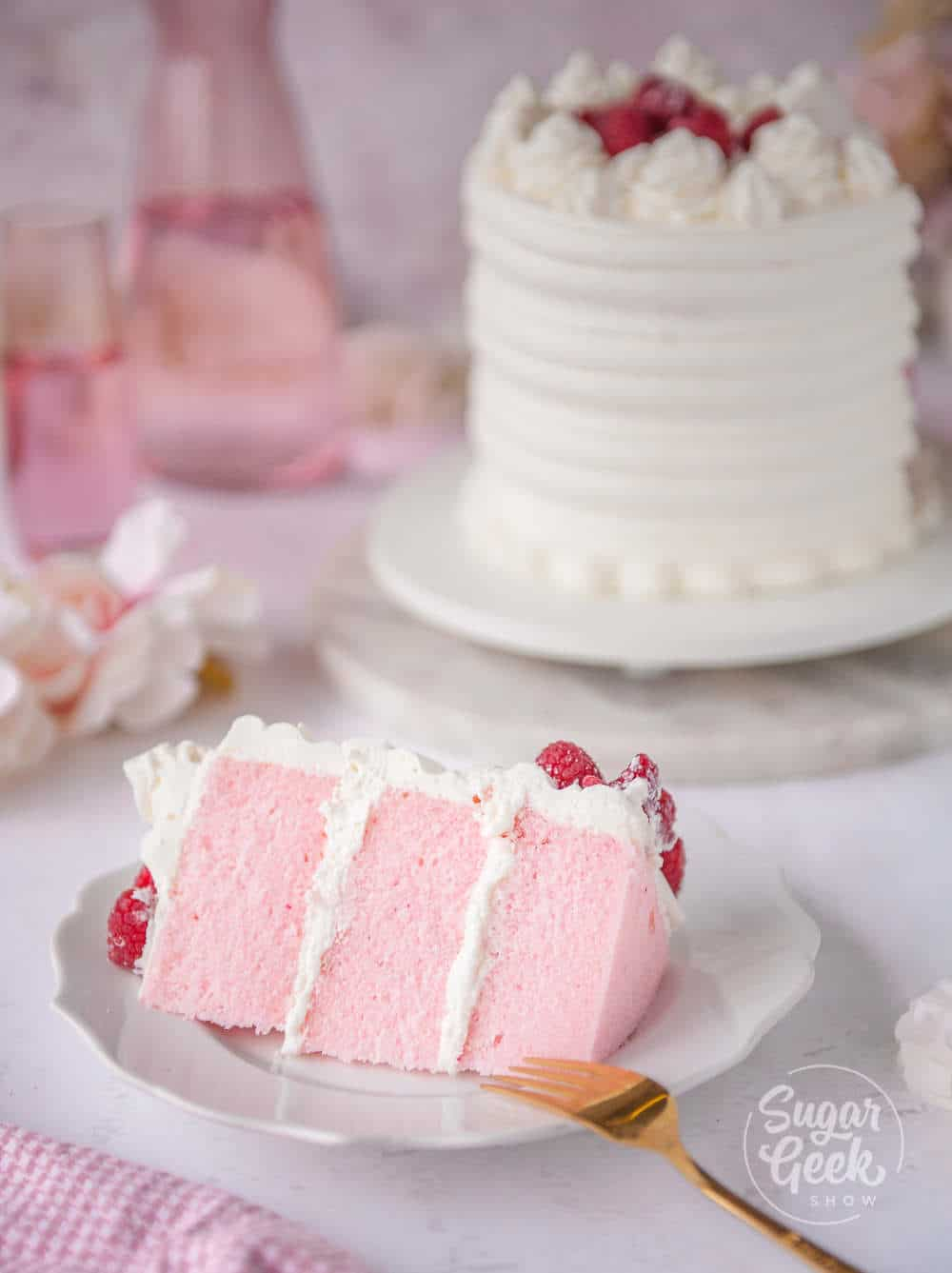 slice of pink velvet cake on a white plate in front of pink velvet layer cake in the background
