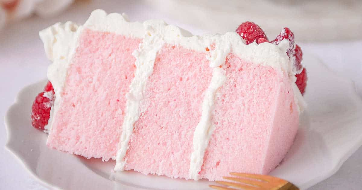 slice of pink velvet cake on a white plate with fresh raspberries