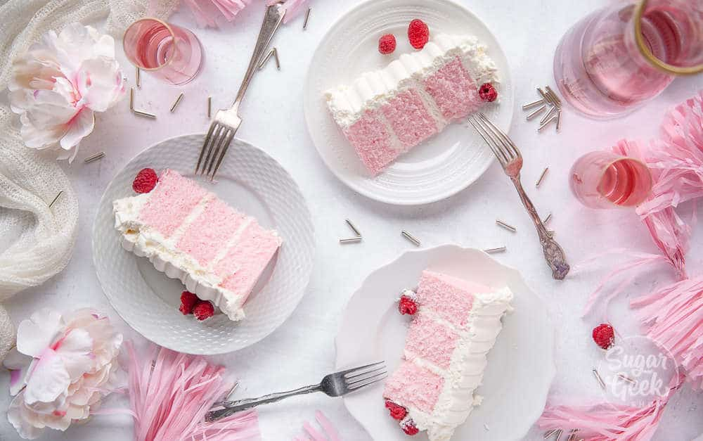 three slices of pink velvet cake on white plates shot overhead