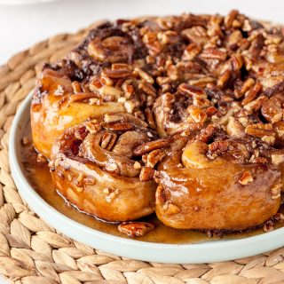 homemade sticky buns on a blue plate on top of a natural woven placemat
