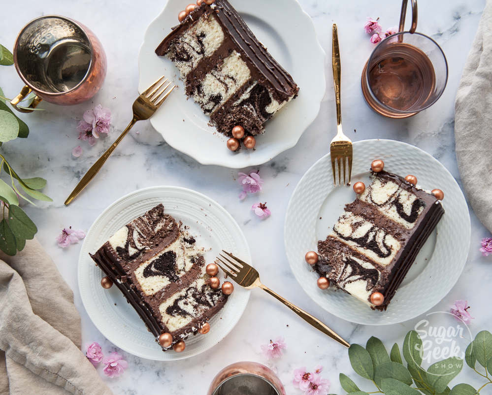 three slices of marble cake on three white plates with gold forks. Shot from above. Surrounded by three copper mugs, greenery and cherry blossoms