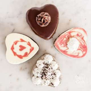 four mini heart cheesecakes on a marble background