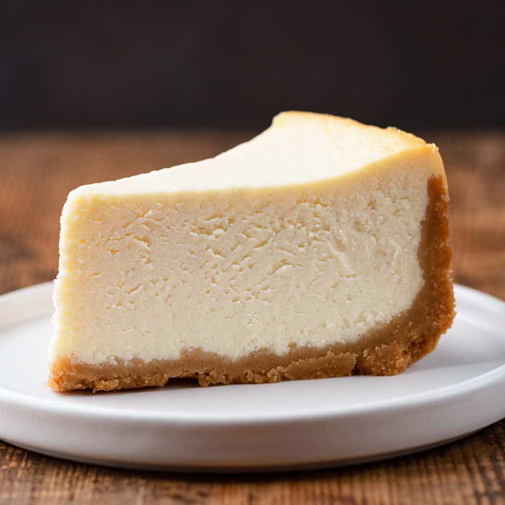 slice of New York cheesecake on a white plate with wooden background