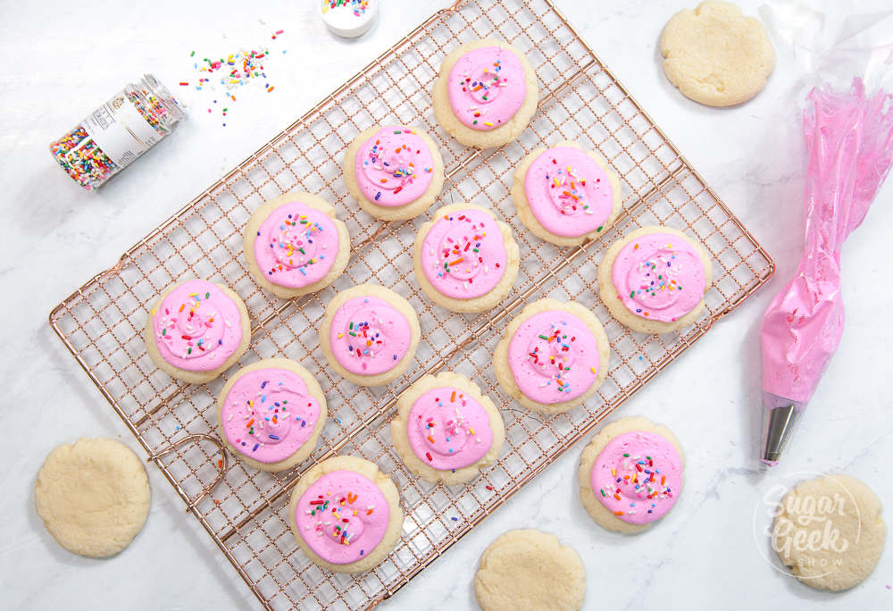 lofthouse cookies on a cooling rack with pink buttercream and sprinkles. Piping bag and sprinkles container off to the side