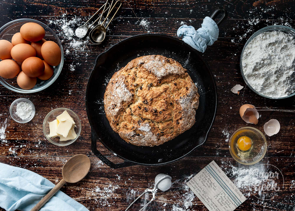 Irish soda bread in a cast iron pan surrounded by ingredients on a wooden backdrop
