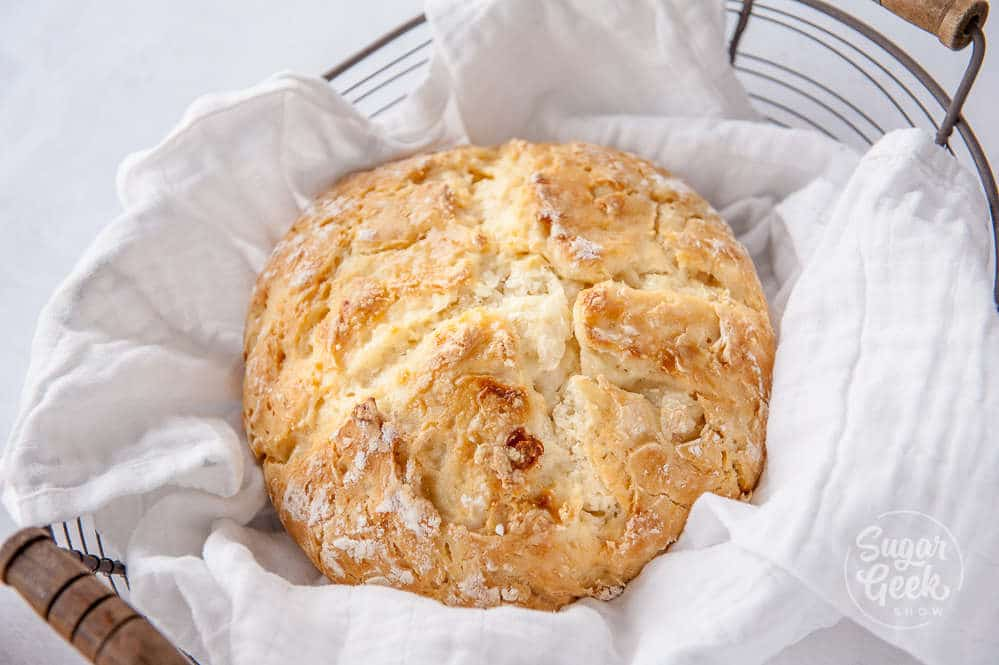 traditional irish soda bread wrapped in white fabric in a basket