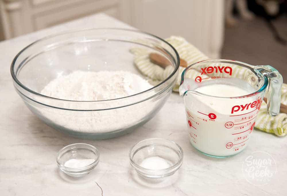 traditional irish soda bread ingredients in clear bowls and a measuring cup