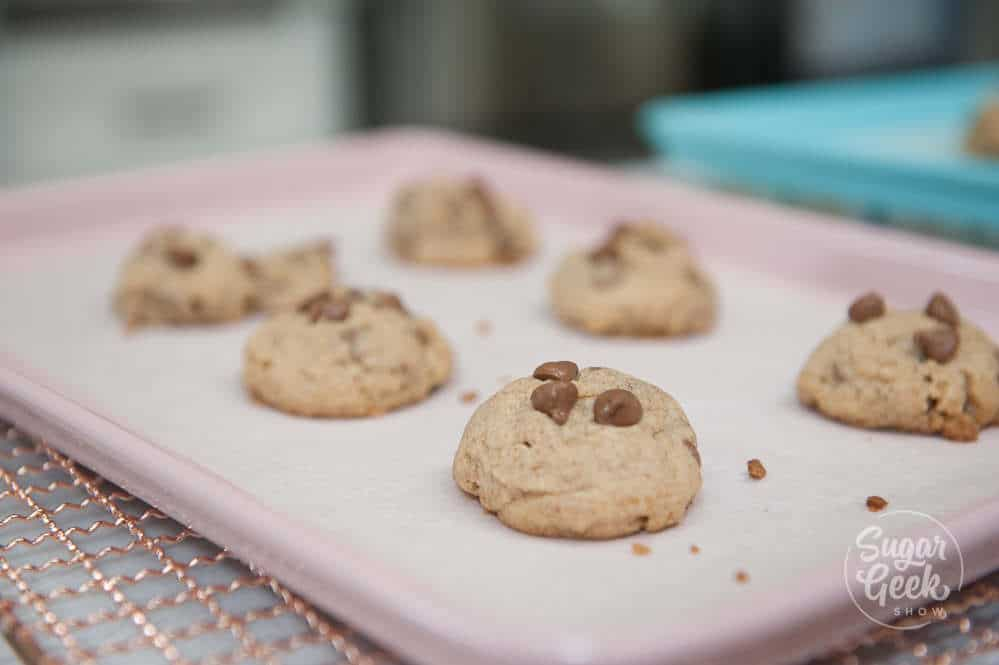 chocolate chip cookies with too much flour on a pink baking sheet