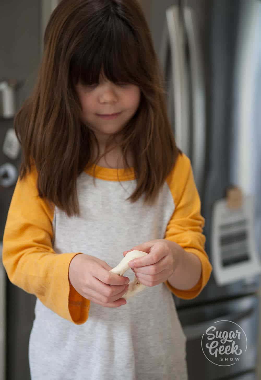 Little girl with brown shoulder-length hair and white and yellow shirt shaping a bagel with her hands