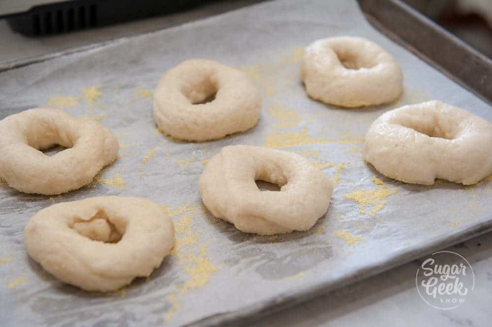 freshly boiled bagels on a sheet pan with parchment paper and cornflour