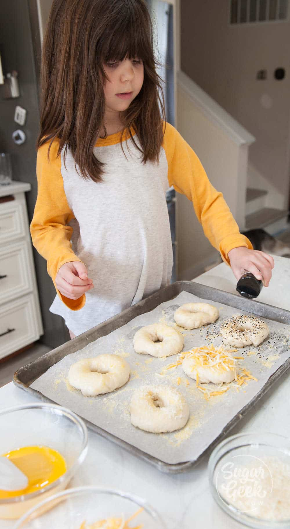 little girl with shoulder-length brown hair and yellow and white shirt sprinkling toppings onto bagels on a sheet pan