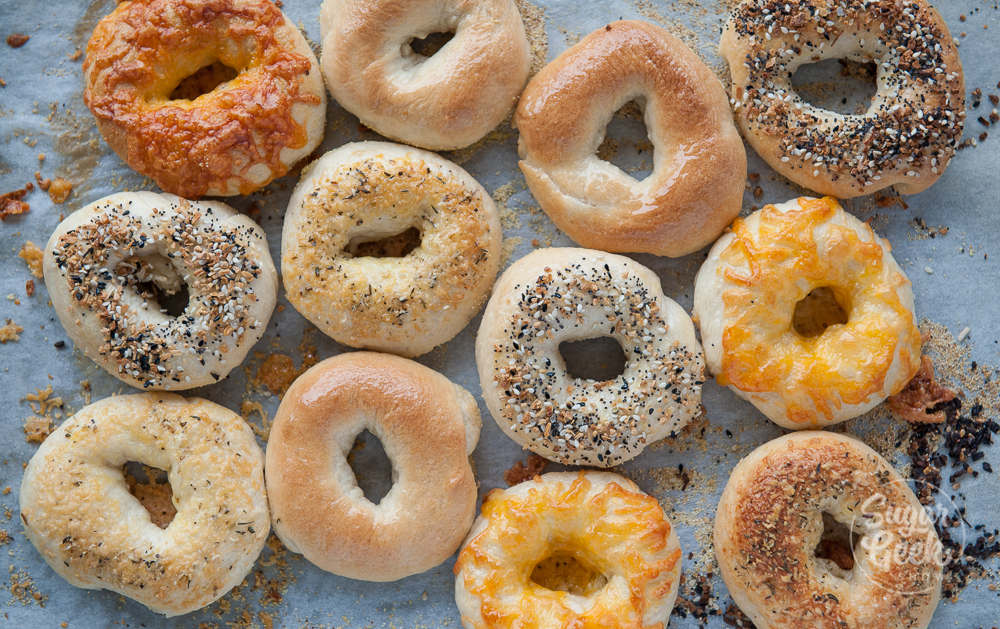 easy homemade bagels with different toppings on a sheet pan