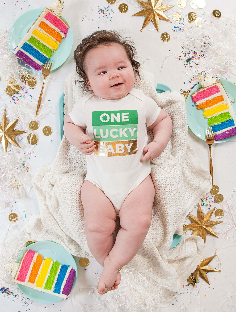 6 month old baby boy on white background with rainbow cake slices around him