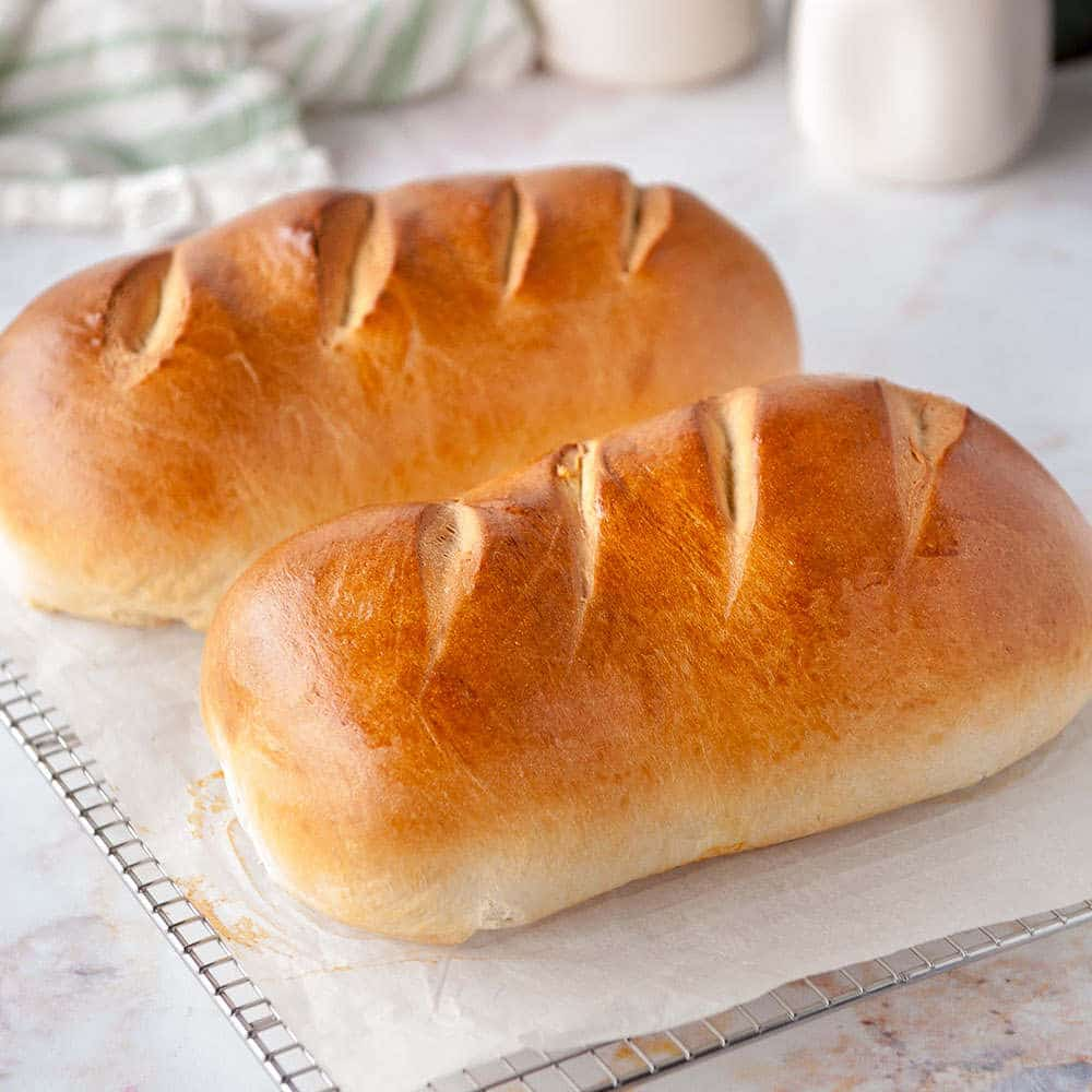two loaves of homemade bread on cooling a rack on a white background