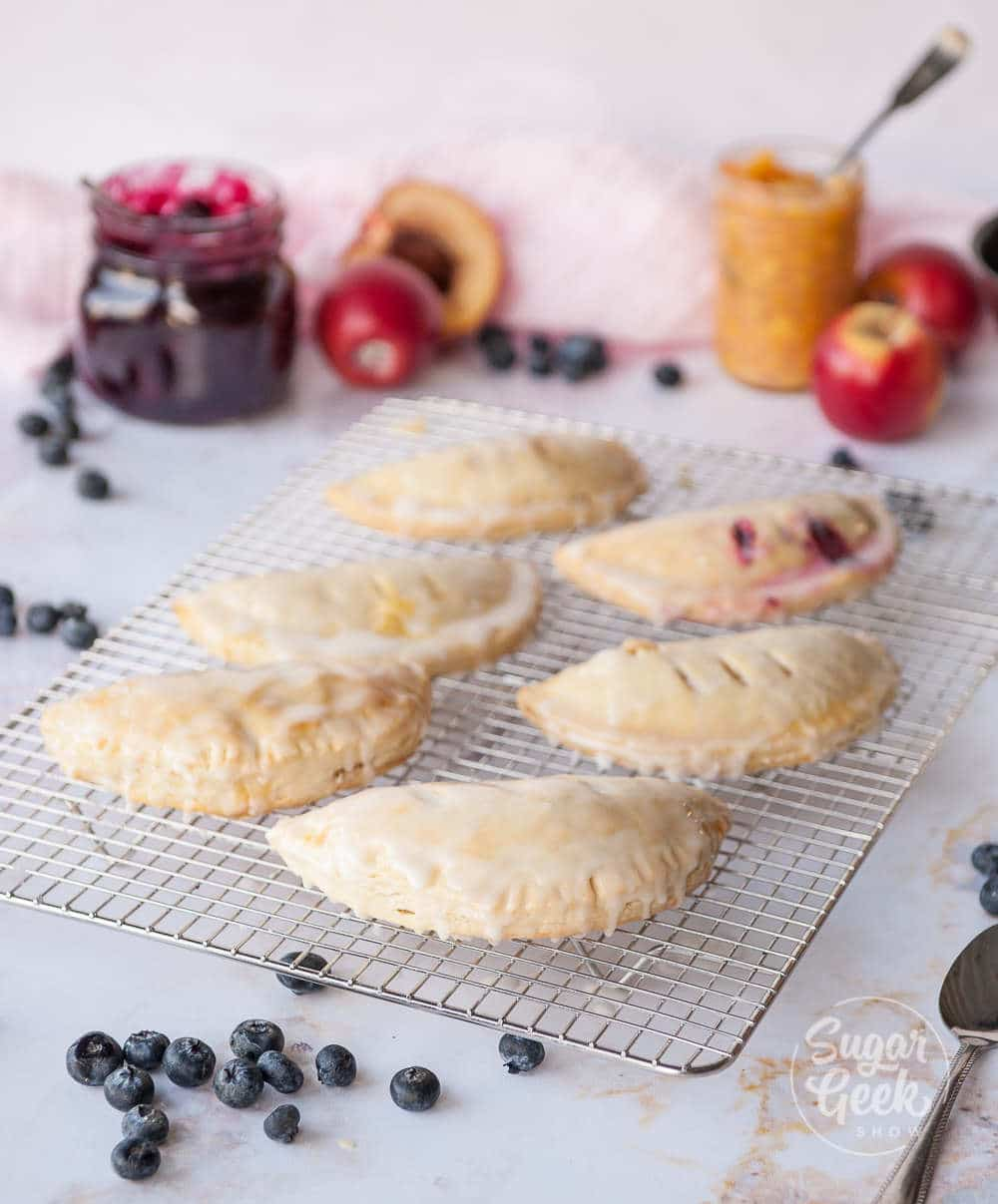 hand pies on a cooling rack with ingredients surrounding them