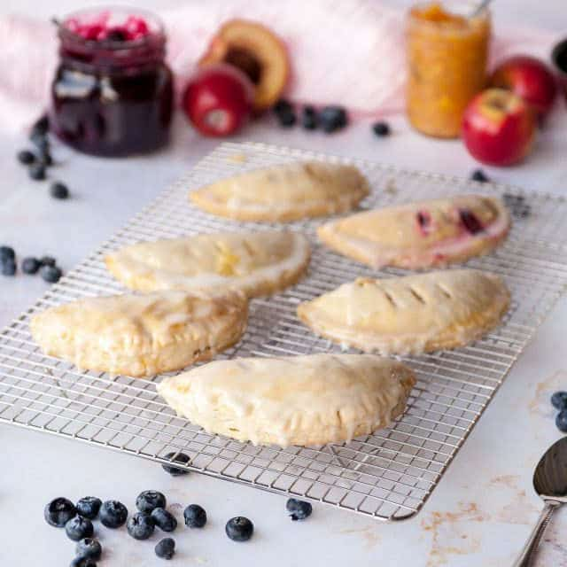 hand pies on a cooling rack on white background with blueberries and fresh fruit in the background