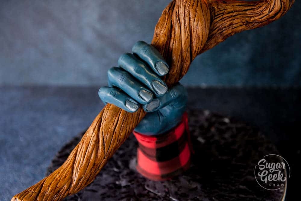 close up of modeling chocolate hand holding wizard staff