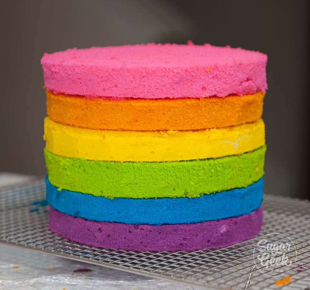 layers of rainbow cake stacked on top of each other