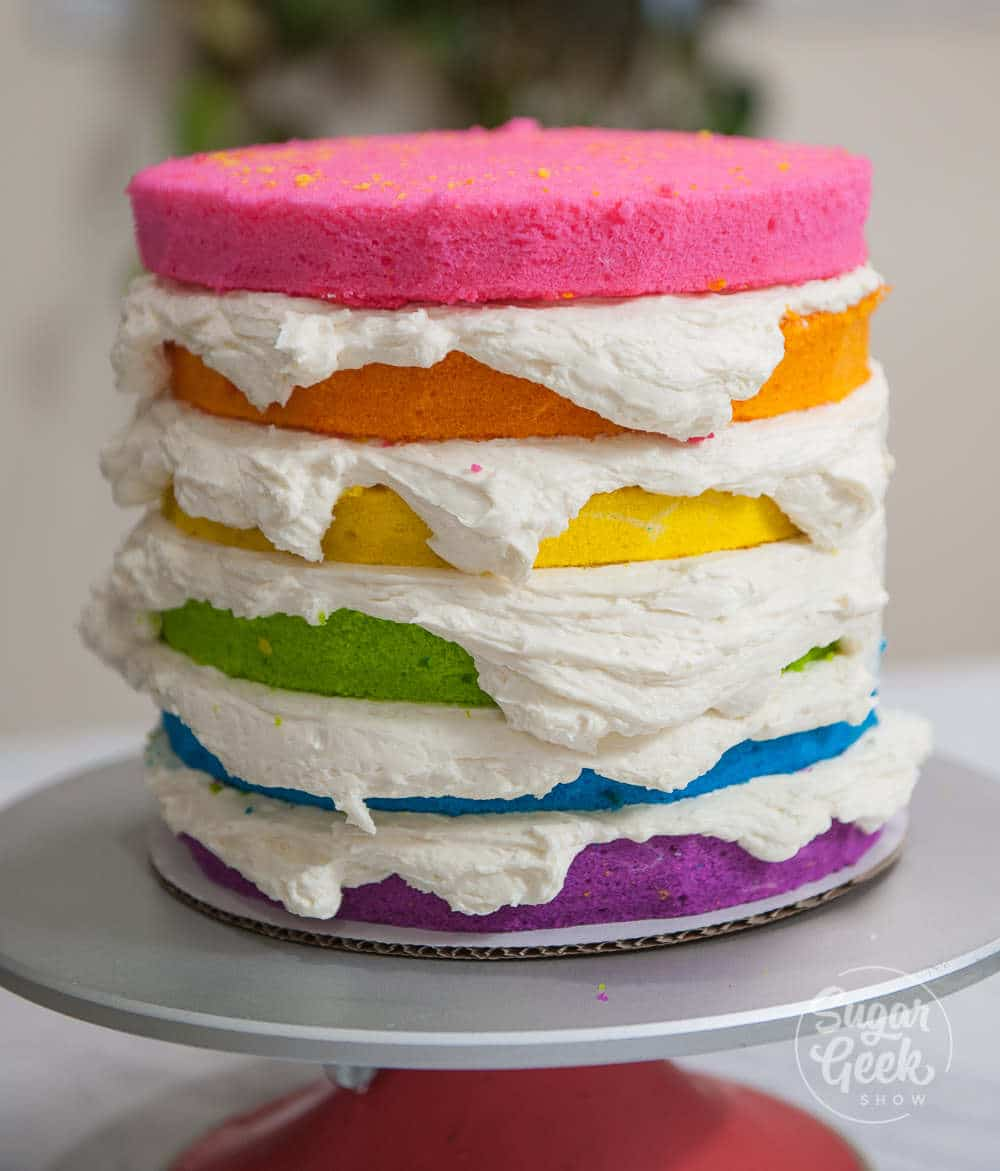 layers of rainbow cake with buttercream frosting in between