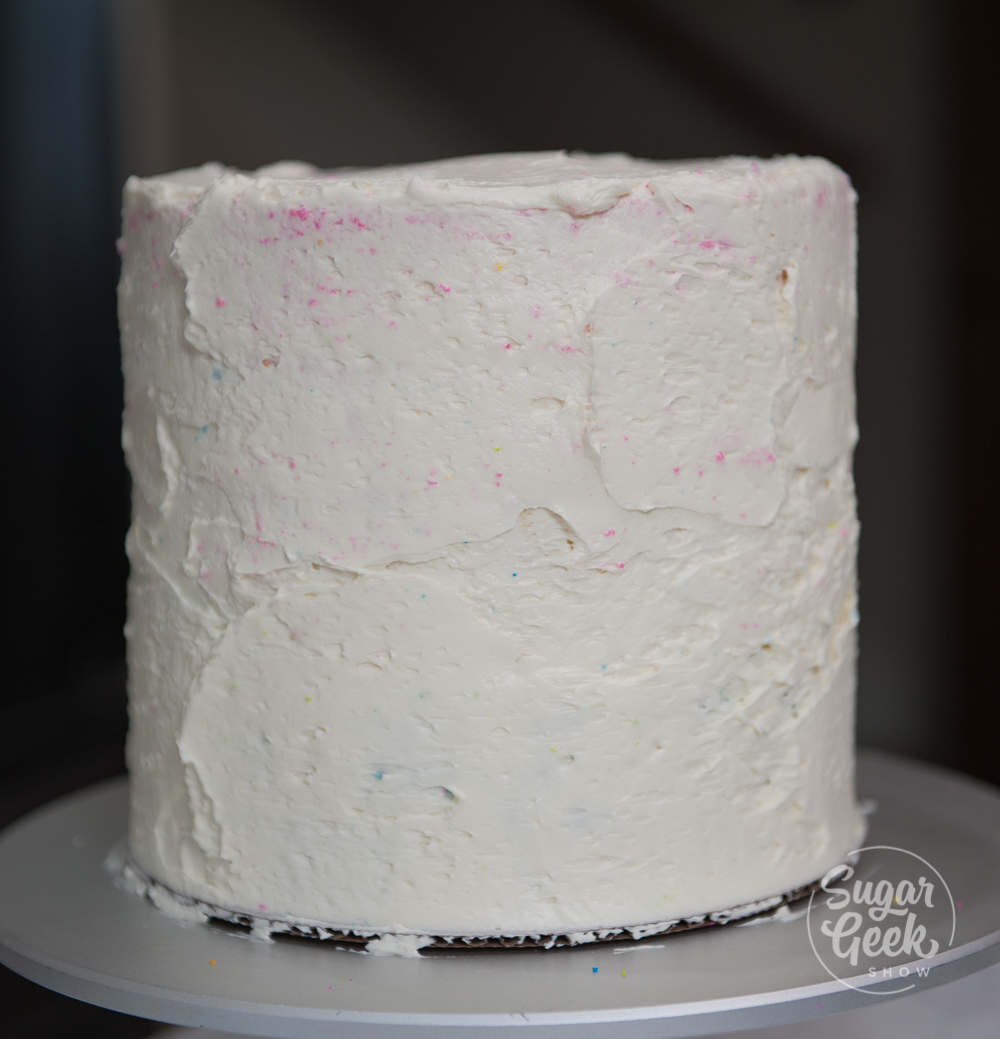 rainbow cake with layer of frosting for the crumb coat