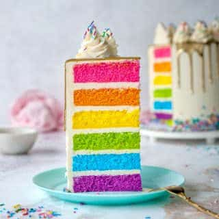 slice of rainbow cake on blue plate white background and whole cake in background
