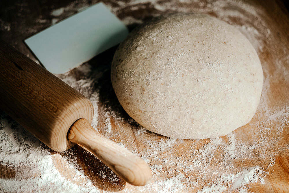whole wheat bread dough on floured wooden surface with rolling pin
