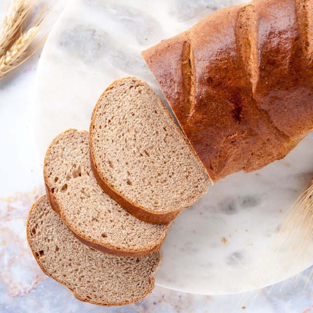 loaf of honey whole wheat bread shot from above with three slices in front on a white background