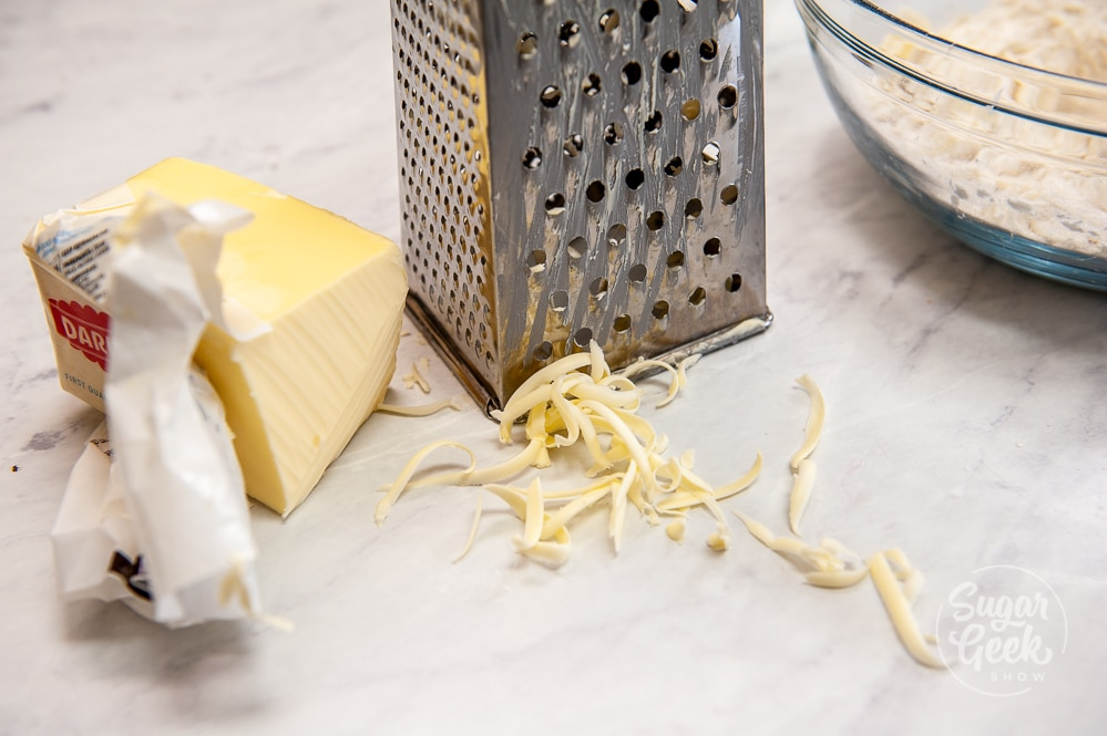 cold grated butter in front of a metal grater on white countertop