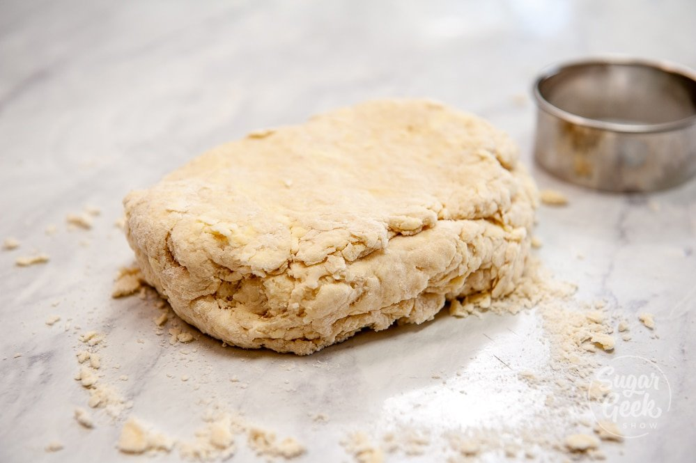 rough biscuit dough folded in half on white countertop