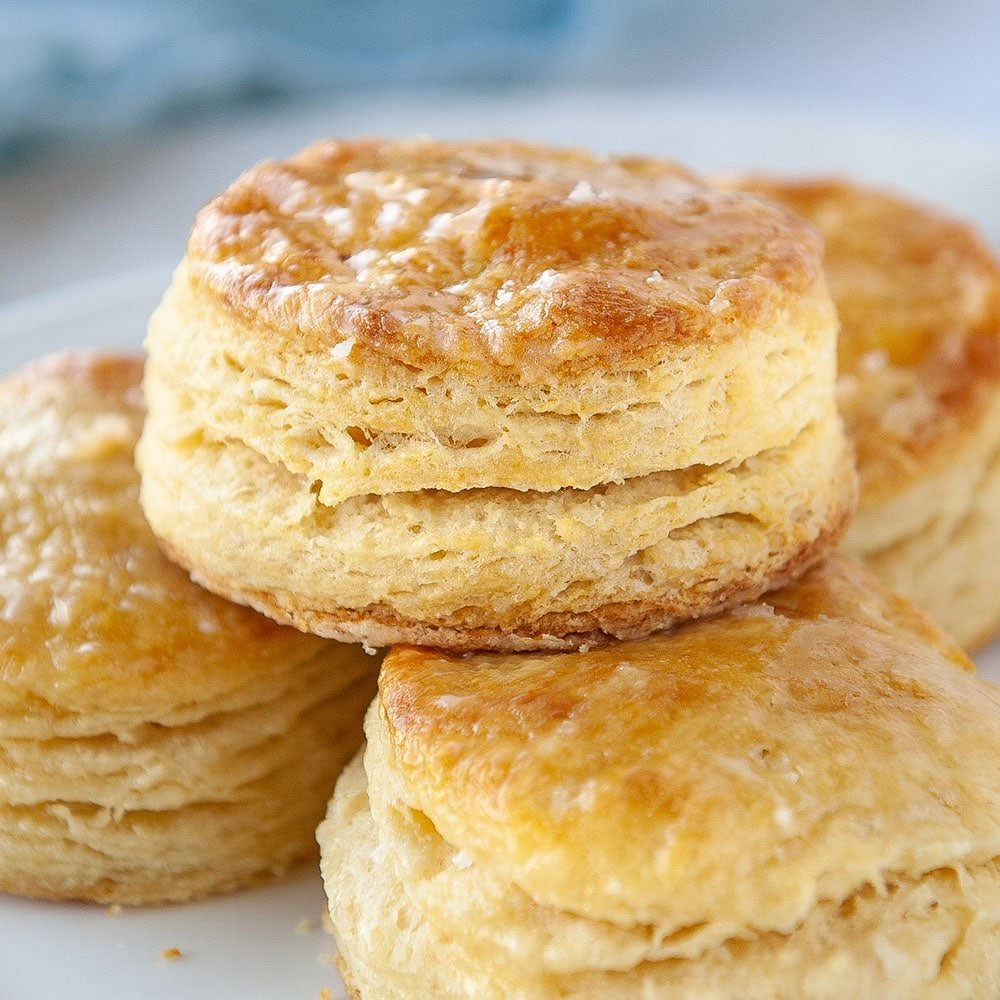 closeup of flaky buttermilk biscuit on top of other biscuits