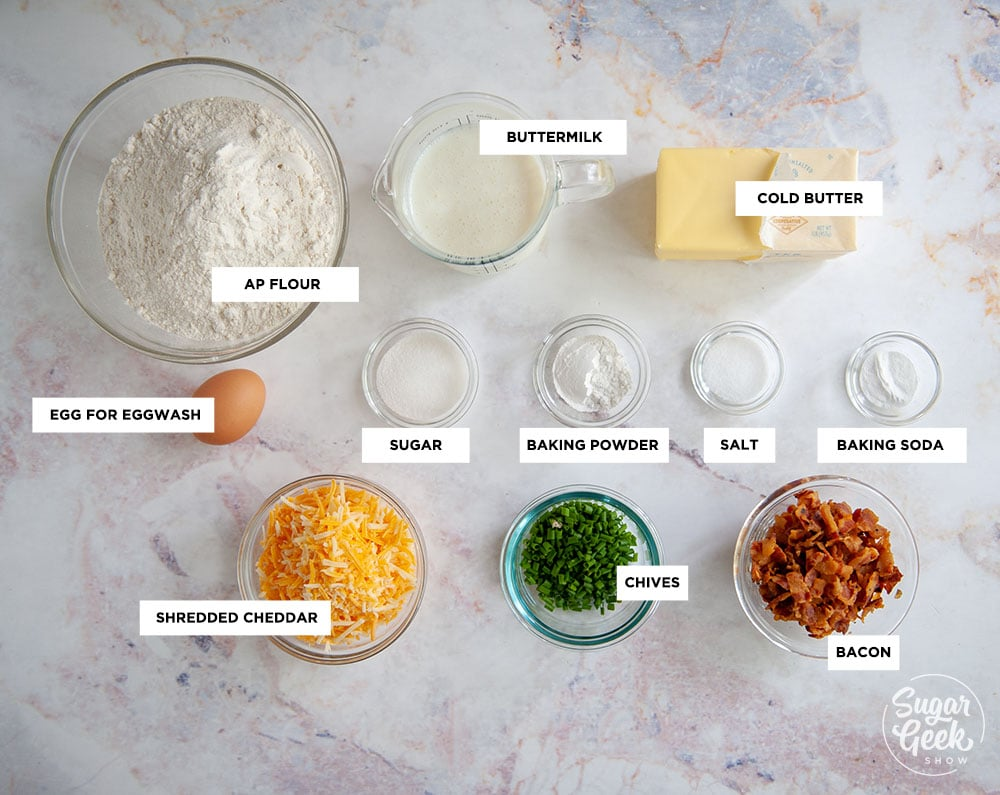 ingredients needed to make bacon cheddar chive biscuits in clear bowls shot from above