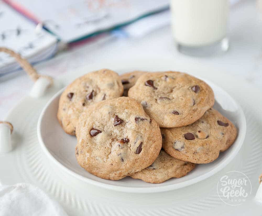 classic chocolate chip cookies in a white bowl on a white background with school book and milk in the background