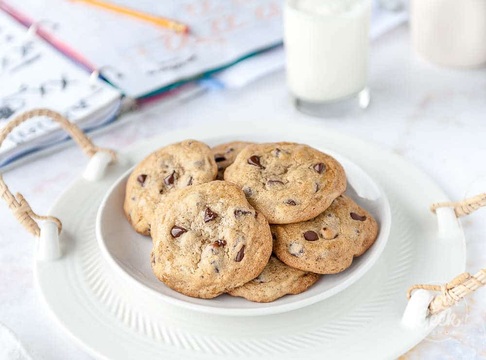 plate of chocolate chip cookies in a white bowl with. schoolbook and glass of milk behind it
