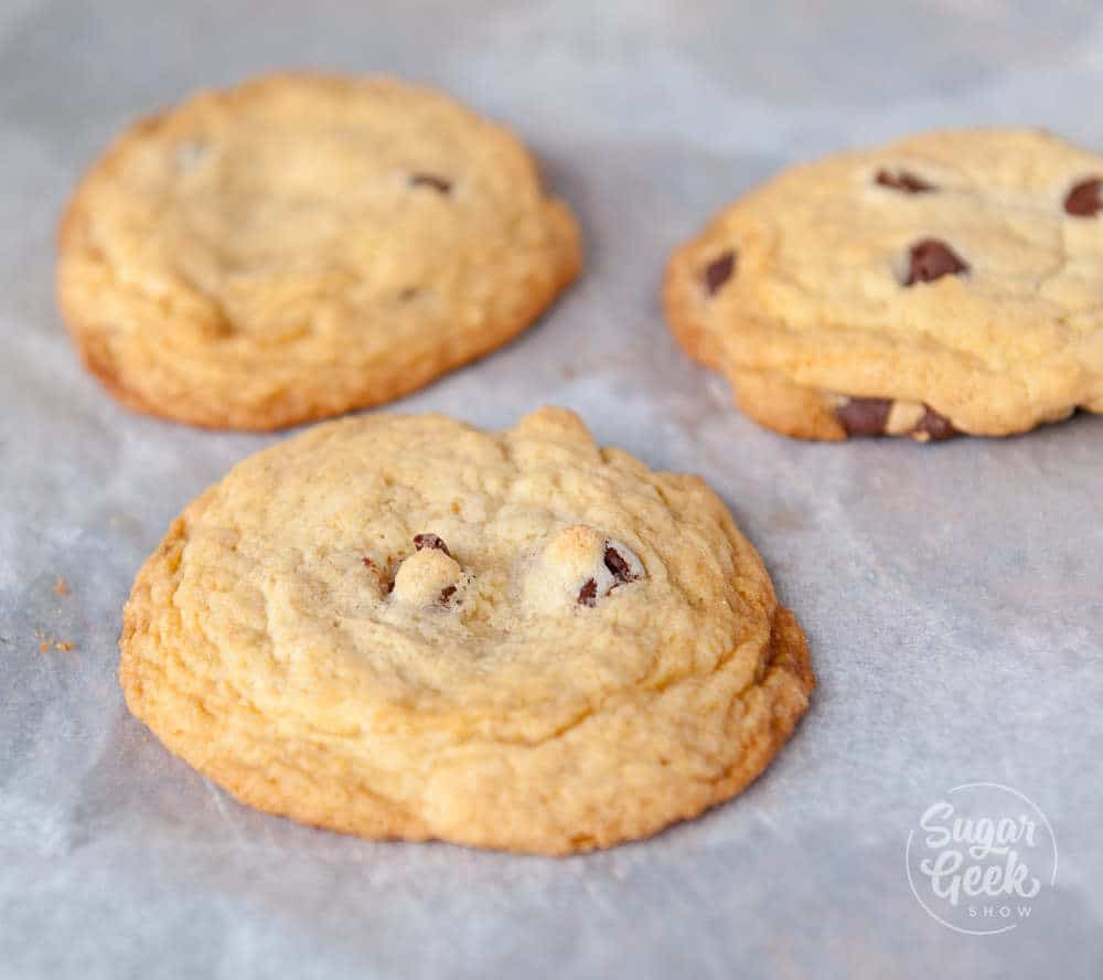 Chocolate chip cookies with extra flour added on a parchment paper lined baking sheet
