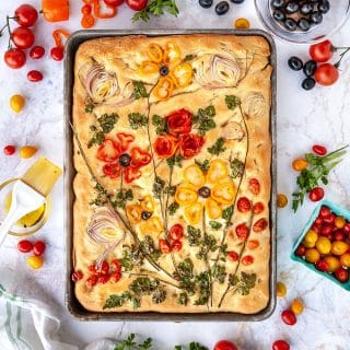 focaccia bread decorated with vegetables to look like flowers shot from above